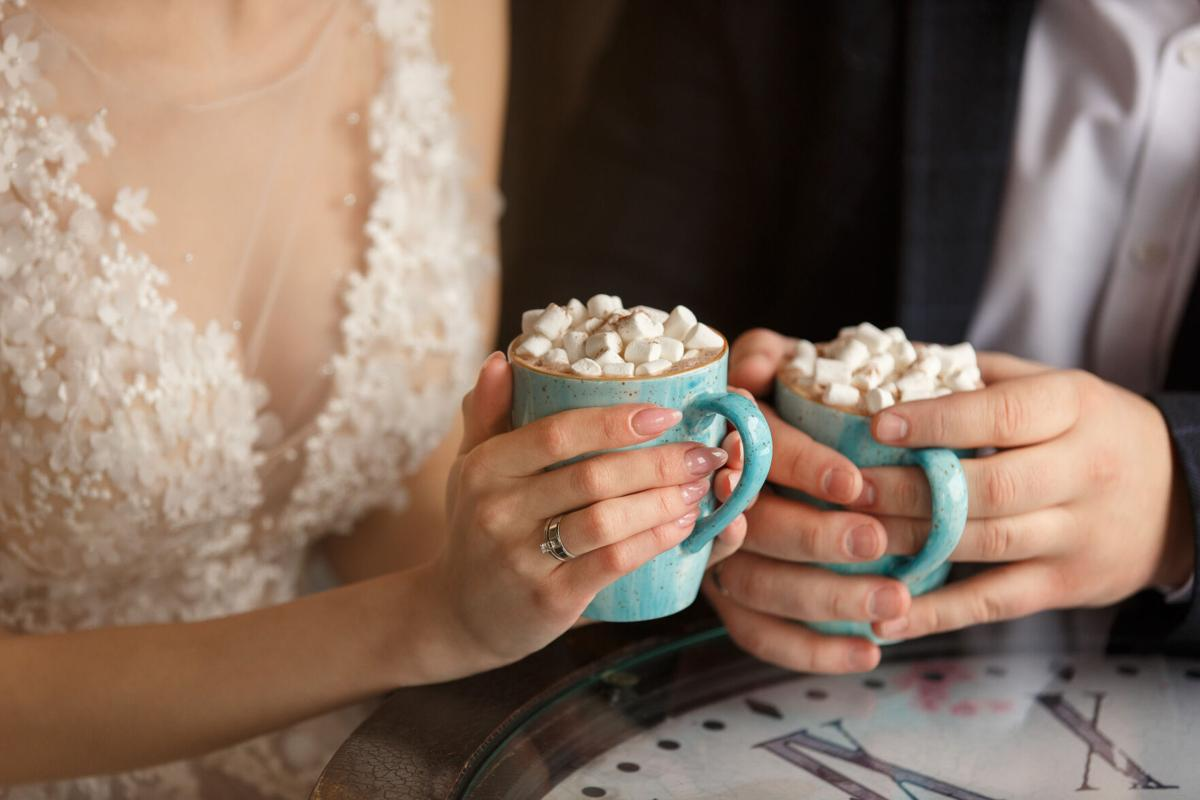Wedding in cold weather. Bride and groom holding cups of coffee with marshmallow in cafe