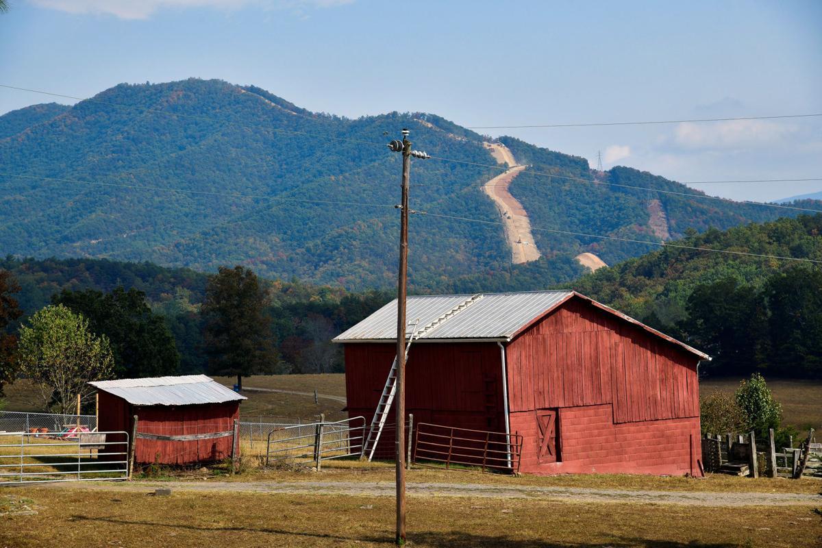 The Mountain Valley Pipeline rises along a ridge behind a rural farm near Elliston