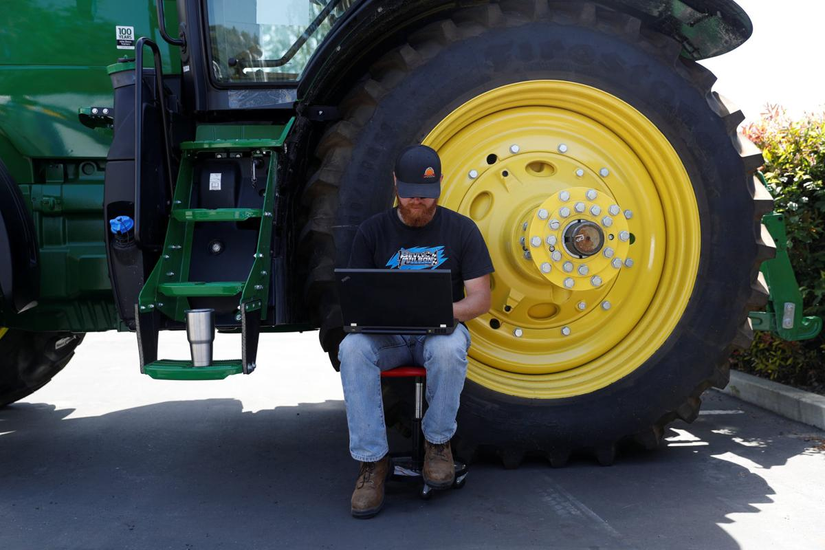 Bryon Majusiak, a senior mechanical engineer with Blue River Technology, works on his computer next to a tractor as others assemble a See & Spray agricultural machine in Sunnyvale, California