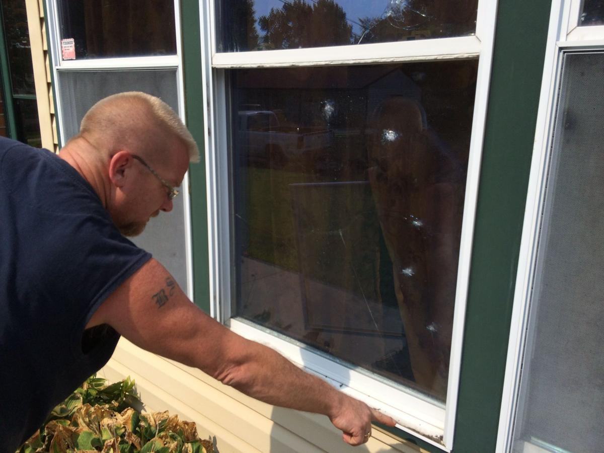 Don Leeser points out BB holes in the front window of his St. Charles County home