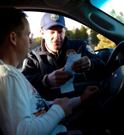 Todd Schmidt, a game warden with the Colorado Division of Wildlife, checks the hunting license of Lee Ramsey during the opening day of the late hunting season in Golden, Colo.