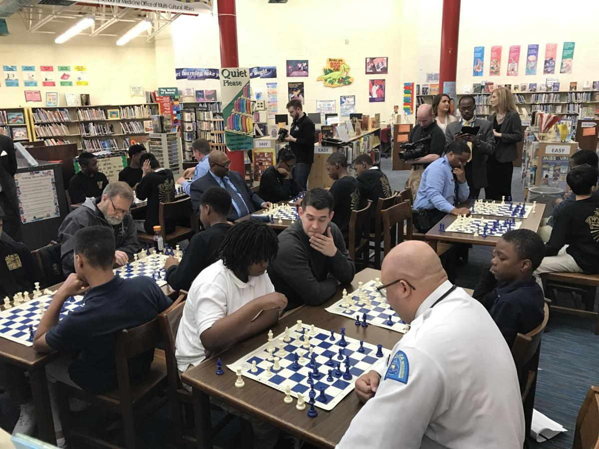St. Louis police officers play chess with public school students