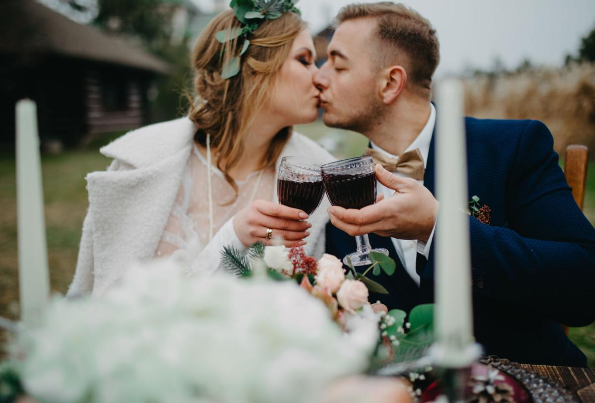 Newlyweds sit near banquet table, clink glasses of wine and kiss.