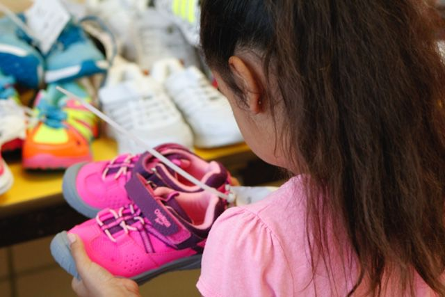 A young girl checking out her new sneakers at LifeWiseStl back-to-school event.JPG