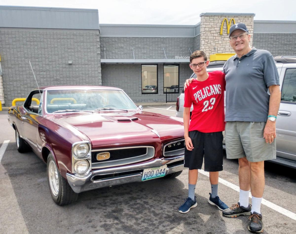 John Blaskiewcz and grandson Sam Cohen standing in front of his 1966 GTO.jpeg