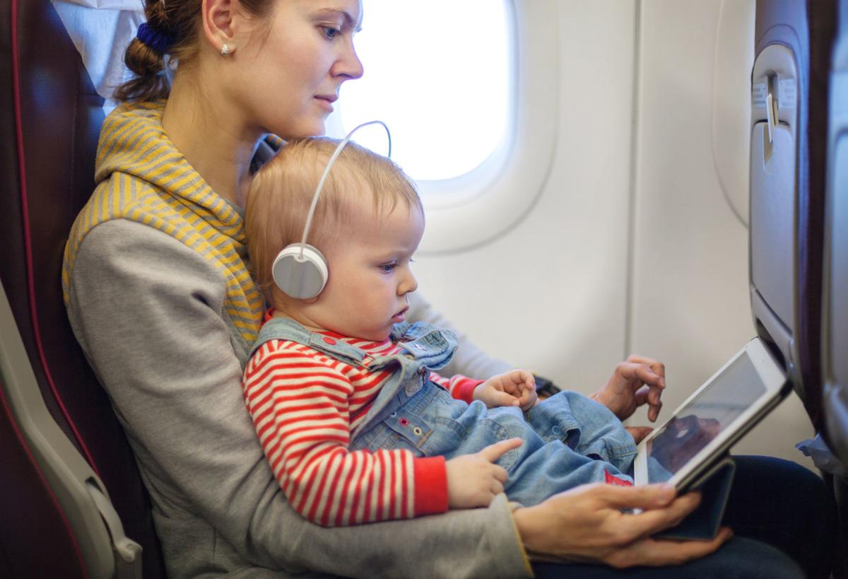 Child sits on lap on airplane