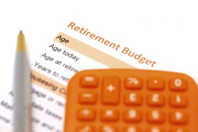 retirement plan document with pen and calculator