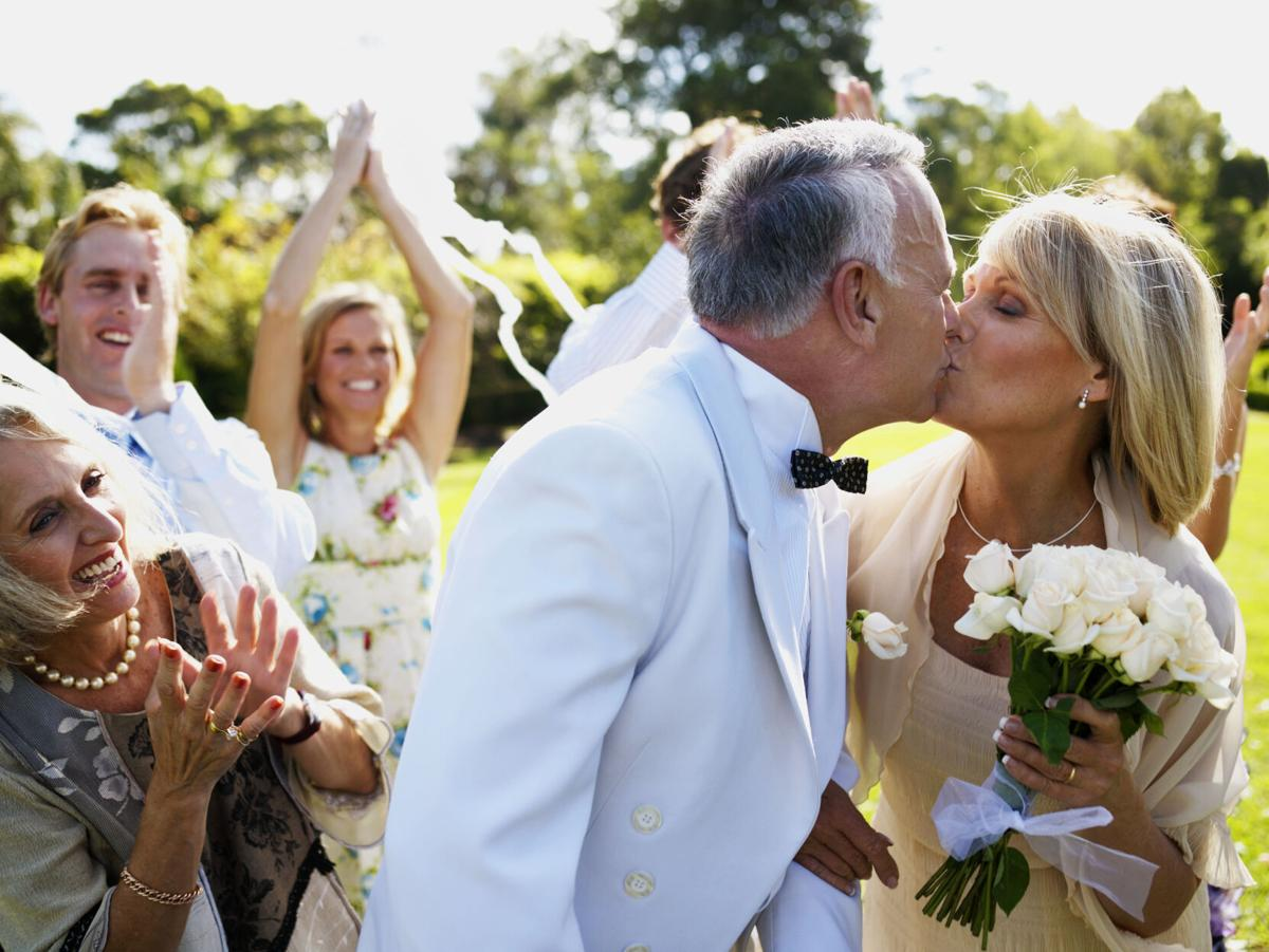 Bride and groom kissing wedding guests in background