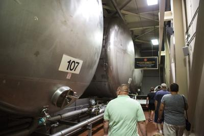 Visitors look at lager tanks at Anheuser-Busch brewery