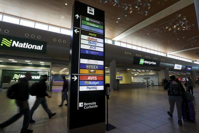 Travelers walk inside Tampa International Airport's Rental Car Center in Tampa, Florida, on March 19, 2021.