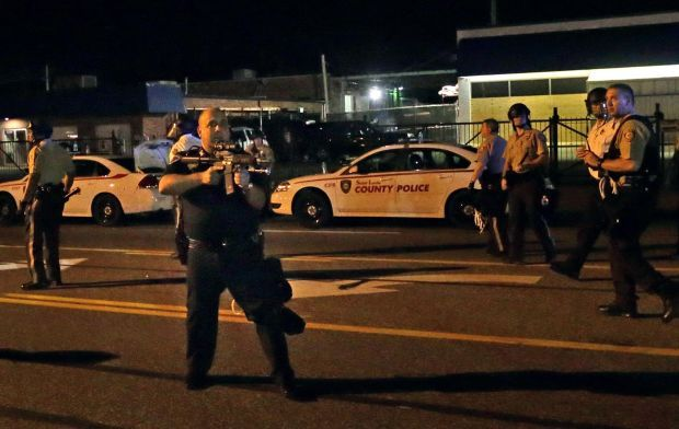 Police points rifle at demonstrators in Ferguson
