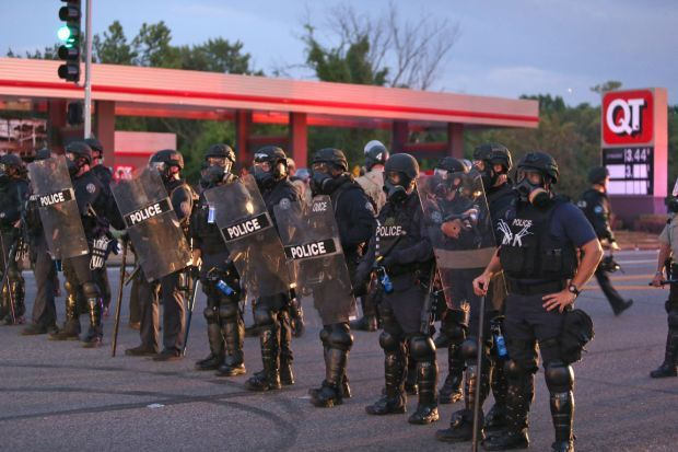 Police in riot gear line up at Ferguson QuikTrip