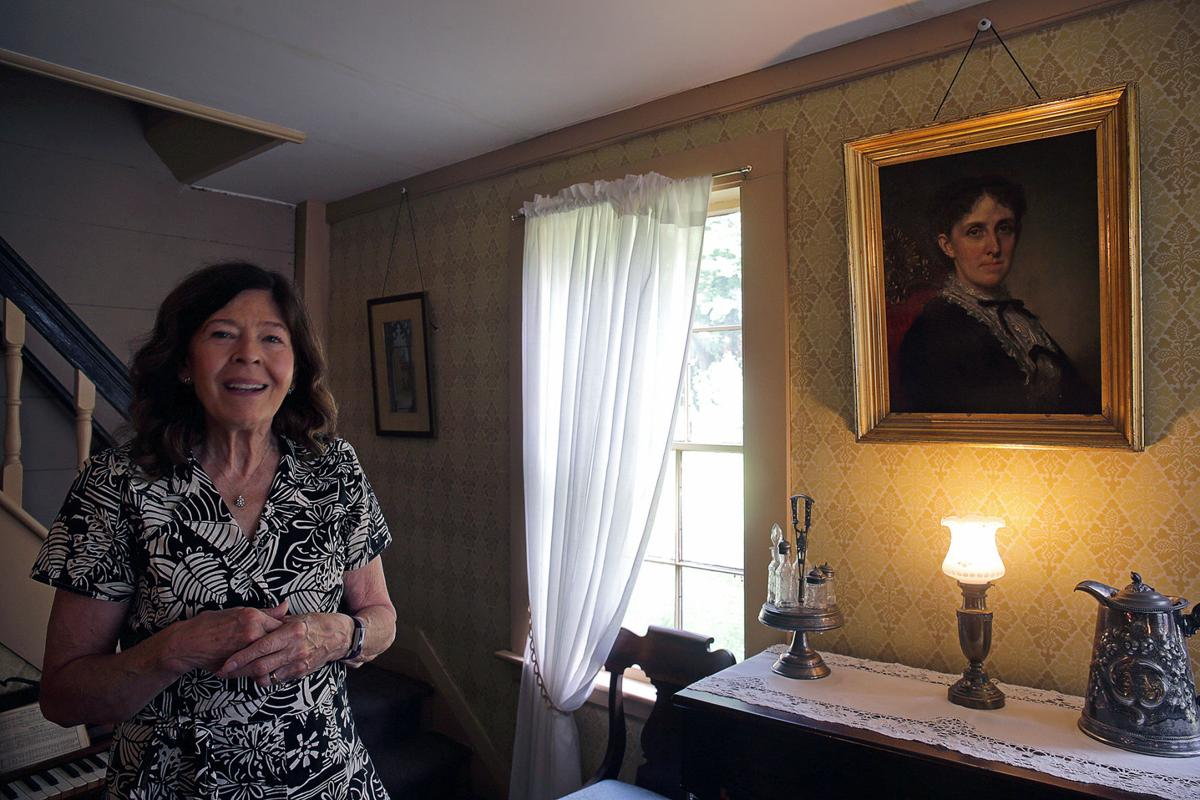 Jan Turnquist, executive director for Louisa May Alcott's Orchard House in Concord, Mass., poses next to a portrait of Louisa May Alcott done by George Healey, a famous portrait painter, on Sep. 11, 2018.