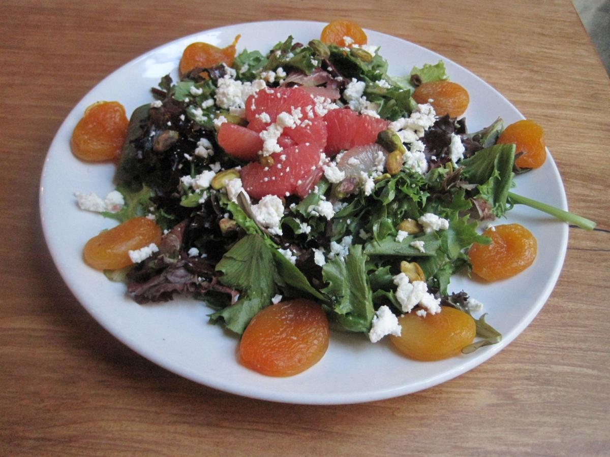 The full-size version of Grapefruit Salad at Bridge, pictured here, features the same ruby red grapefruit supremes, poached apricots, goat cheese, and chopped pistachios on a bed of sprightly greens dressed with a white balsamic vinaigrette as the smaller