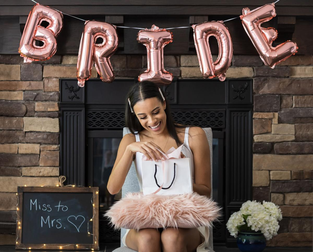 Young beautiful woman opening gift bag at her bridal shower