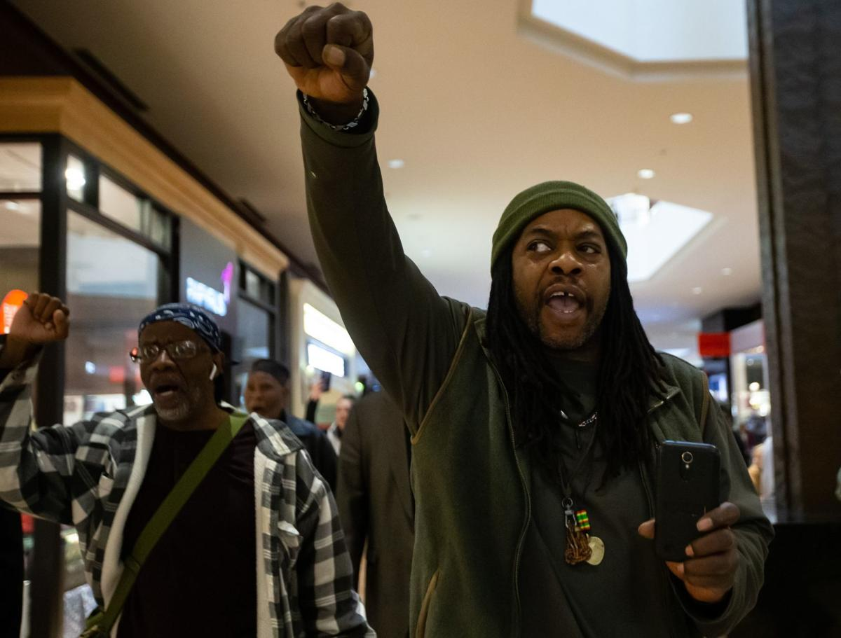 Protesters march in the St. Louis Galleria on Black Friday