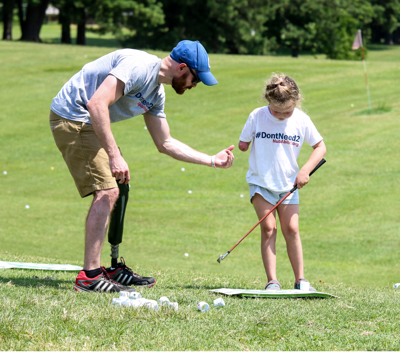 Limb-different coach and child play golf