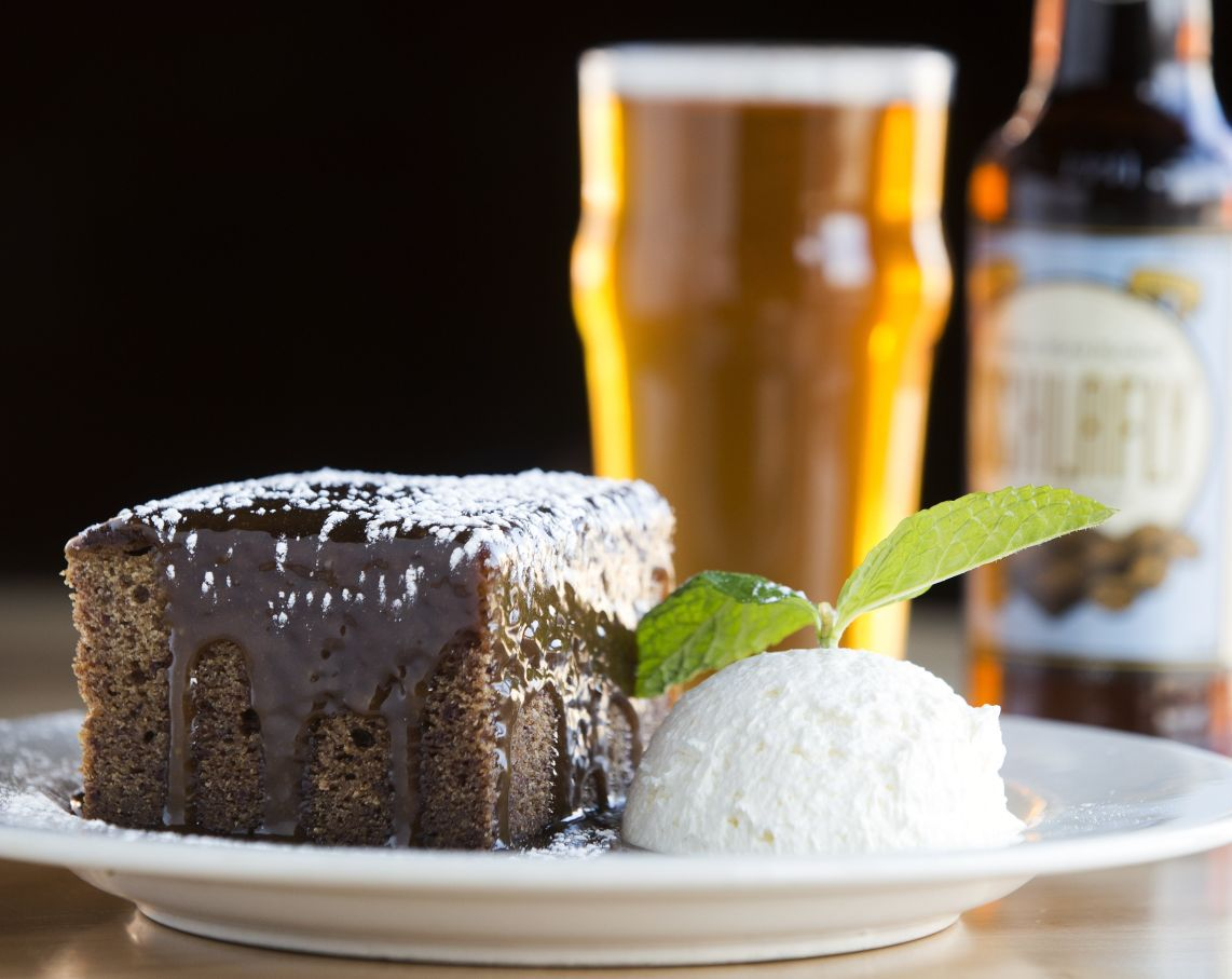 Sticky Toffee Pudding A Scottish Cake Topped With Caramel Sauce Served Freshly Whipped Cream Along Side Schlafly Double Bean Blonde At The