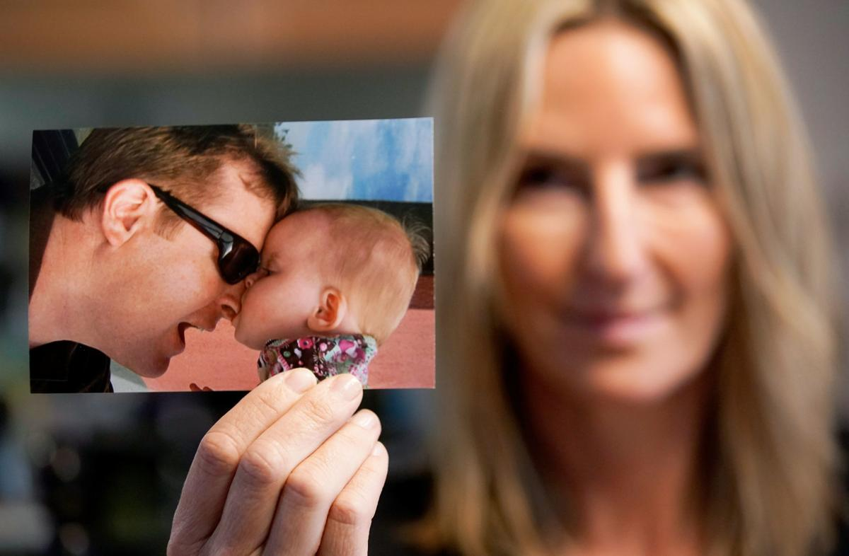 Kelly Pfaff holds a picture of her husband John and his daughter during an interview at her home in Park City