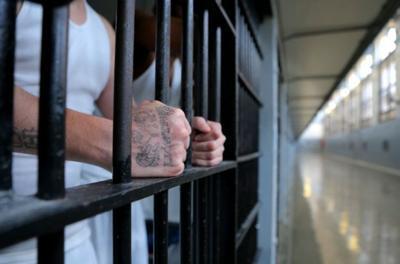 Prisoner grasps bars on his cell