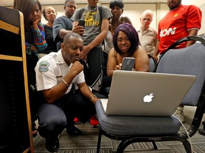 Residents watch video after Ferguson City Council meeting