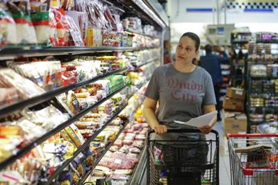 Elba Nunez, who works at Foodsmart Urban Market in Chicago, does grocery shopping for an online order at the store on Tuesday, March 24, 2020.