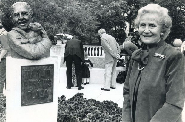 Carol Perkins stands near bust of her husband in Forest Park