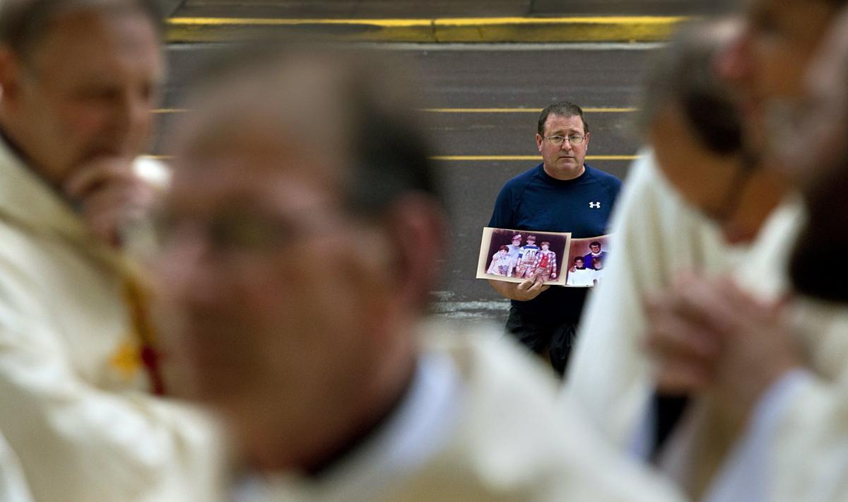 Abuse survivor stands alone outside Cathedral Basilica during Mass of Reparation