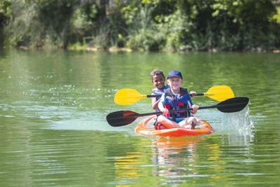 Two little boys kayaking down a beautiful river