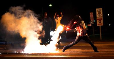 Protester throws tear gas container during Ferguson protests