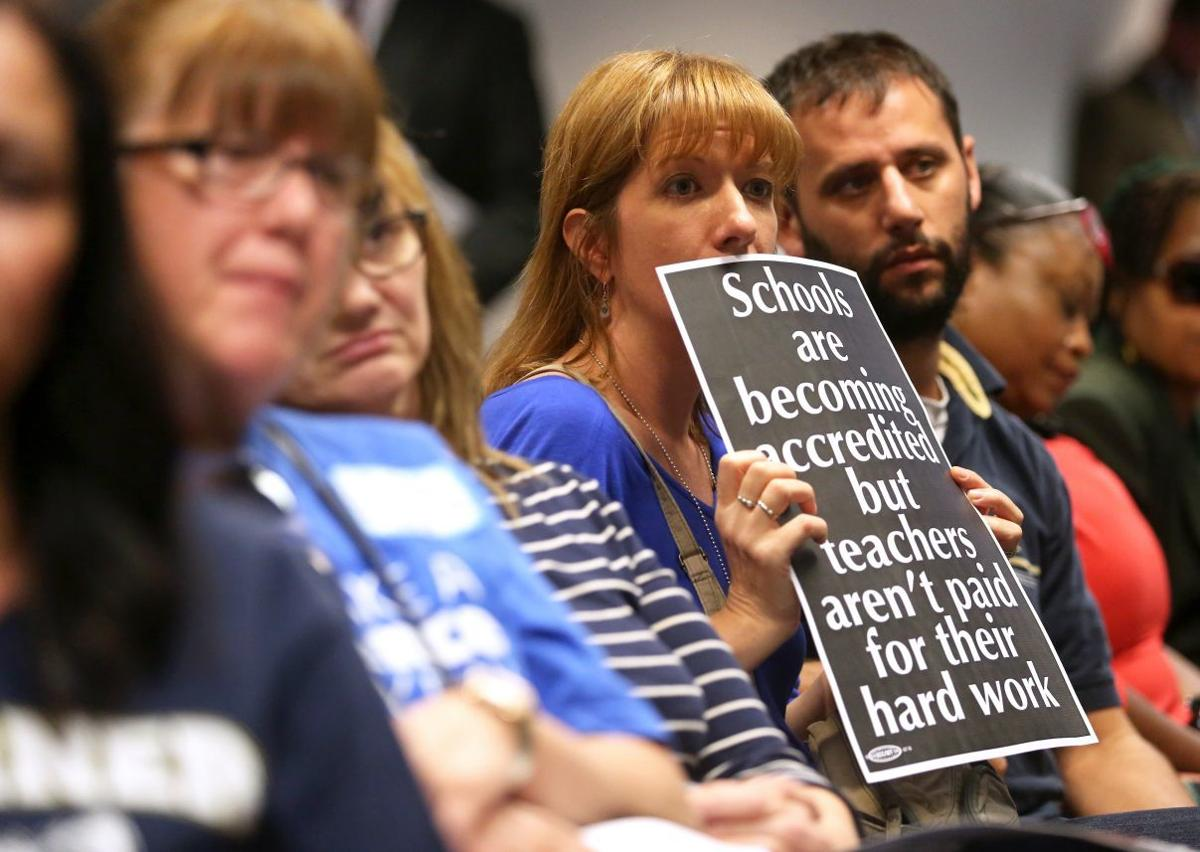 St. Louis teachers hold sign protesting stagnant salaries