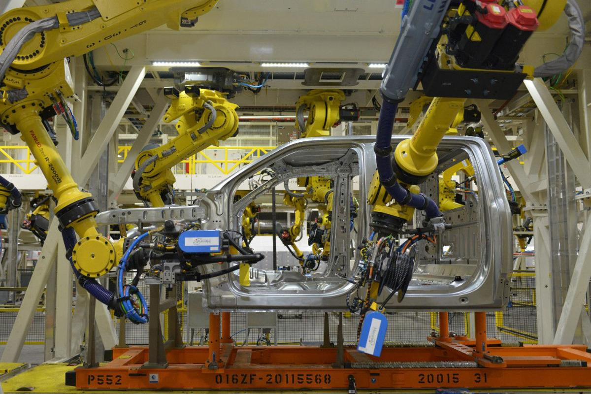 Assembly of the Ford F-150 at the company's Dearborn Truck Plant. One of the few human-specific jobs here is refilling a machine's parts supply.