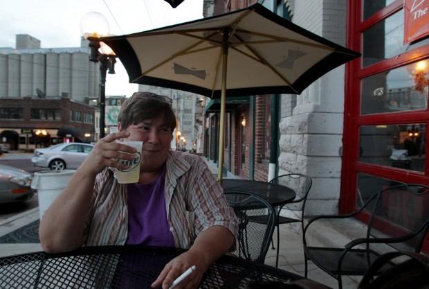 Woman smokes on patio at Firehouse Lounge in Alton