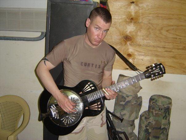 Jake Curtis playing guitar in Iraq