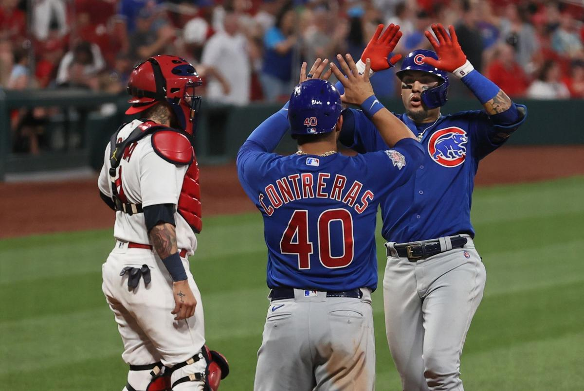 Javier Baez high-fives Willson Contreras after hitting a homer in a Cardinals vs. Chicago Cubs game.