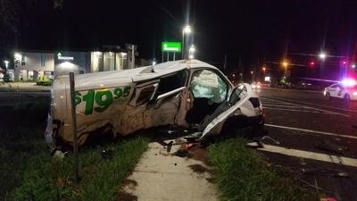 Driver runs red light, slams moving van