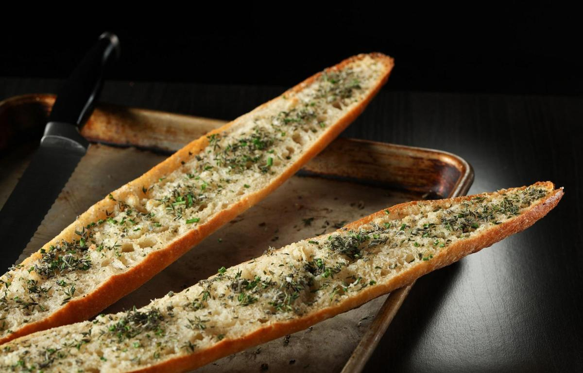 The warm garlic bread is finished with fresh herbs, like sage, thyme, chives and oregano.