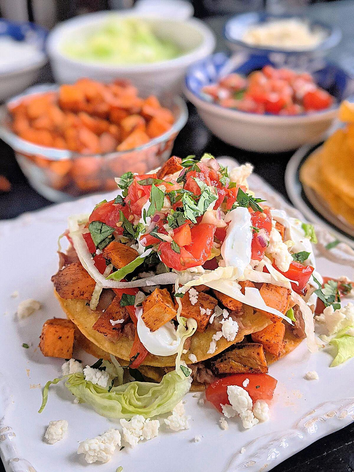 These vegetarian tostadas are stacked with two layers of smashed pinto beans, lettuce, pico and roasted sweet potatoes and bell peppers.