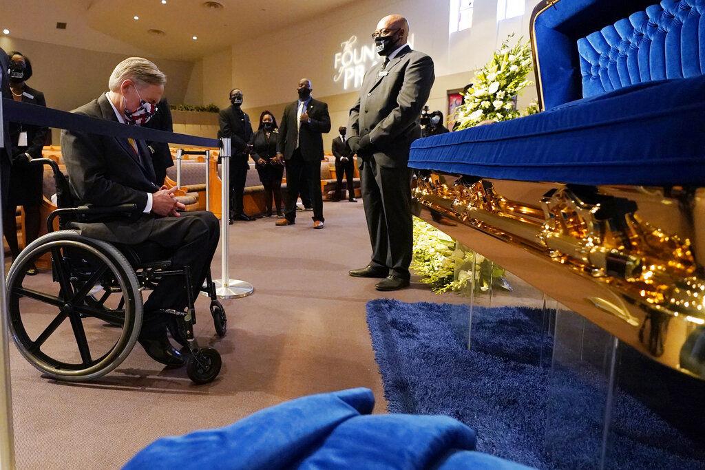 Texas Gov. Greg Abbott passes by the casket
