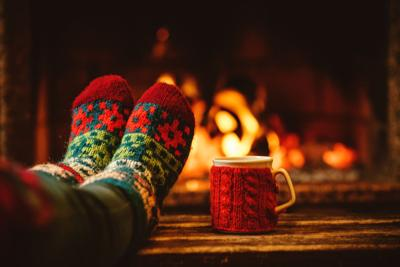 Feet in woollen socks by the Christmas fireplace. Woman relaxes