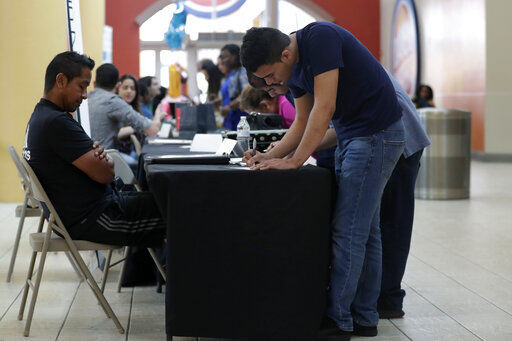 US economy defies threats with a solid job gain for October