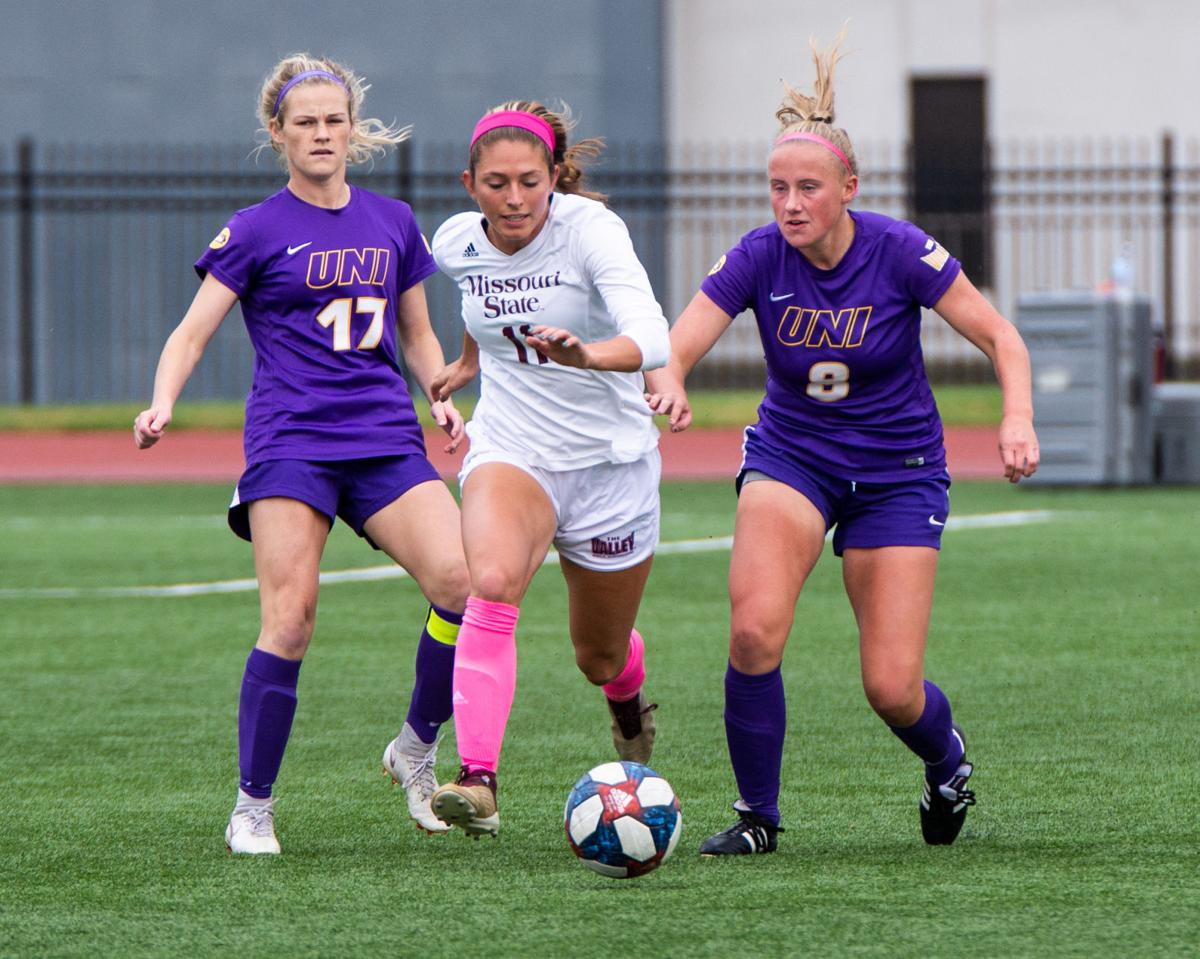 Ashley Coonfield pushes past two UNI defenders
