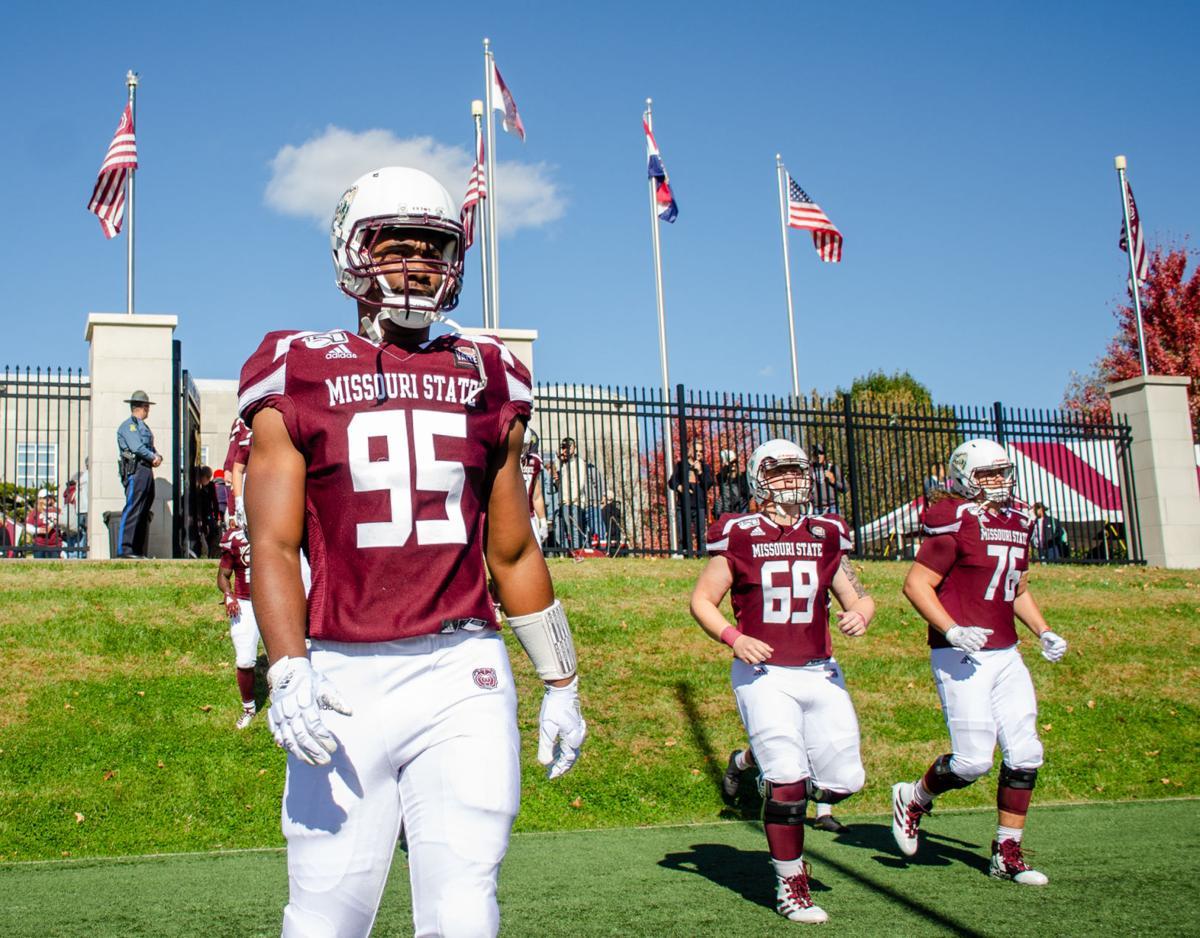 football team walks through the gates