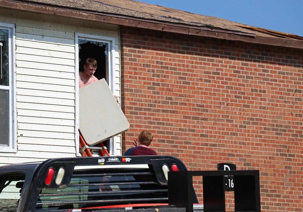 Two young men work to remove a table from their apartment the day after the tornado hit Jefferson City