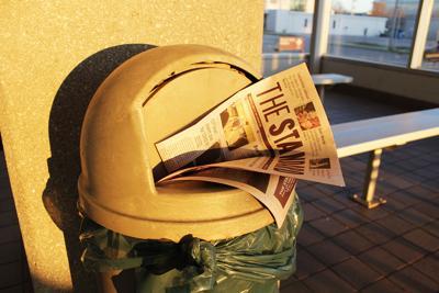 A newspaper sits in a trash can