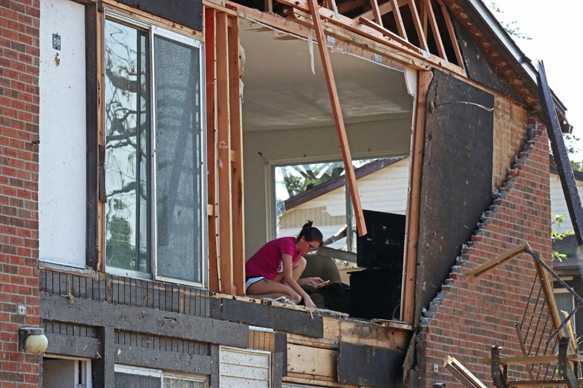 A woman assesses the damage done by the tornado