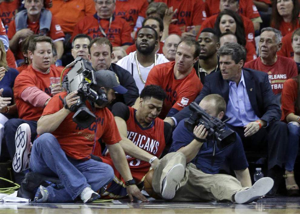Drew Brees makes a big assist - helping Anthony Davis up after a fall in the Pelicans playoff game _lowres