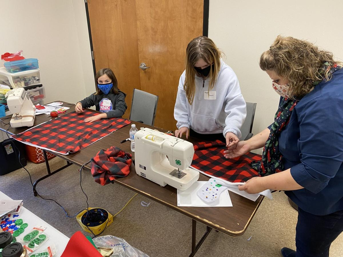 Dawn_Culbreath_assisting_Reagan_Brown_pin_fleece_together_to_make_a_blanket_during_the_Holiday_Sewing_Workshop.jpg