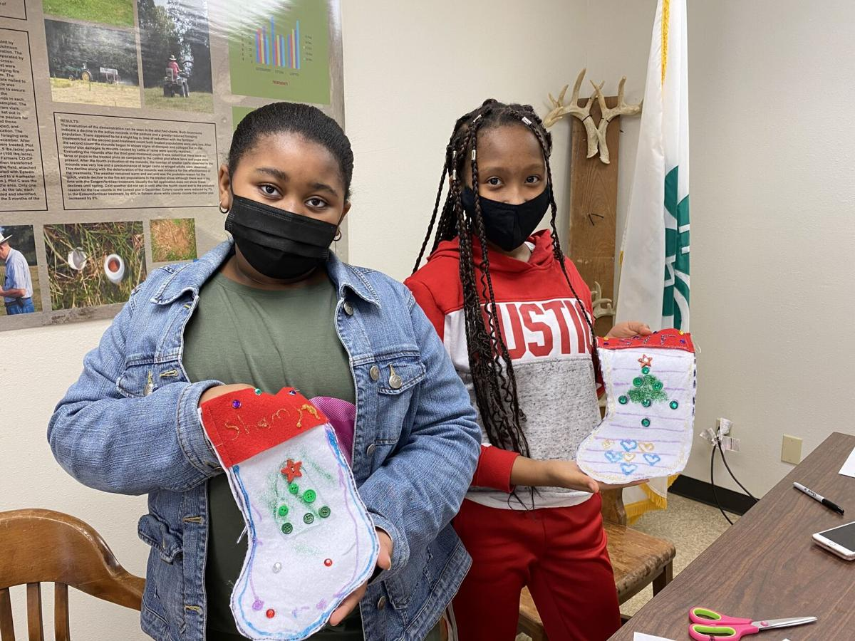 Shamya_Stirgus_and_Selah_Flowers_of_Flowers_Solution_Academy_showing_off_their_stockings_they_made_during_the_Holiday_Sewing_Workshop.jpg