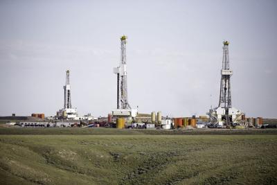 FILE - Fracking derricks